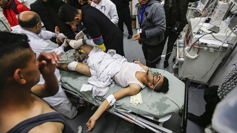 Paramedics treat an injured Palestinian at a hospital in the southern Gaza Strip [Said Khatib/AFP]