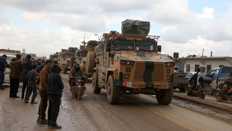 A Turkish military convoy passes through the Syrian rebel-held town of Hazano in Idlib's northern countryside [Aaref Watad/AFP]