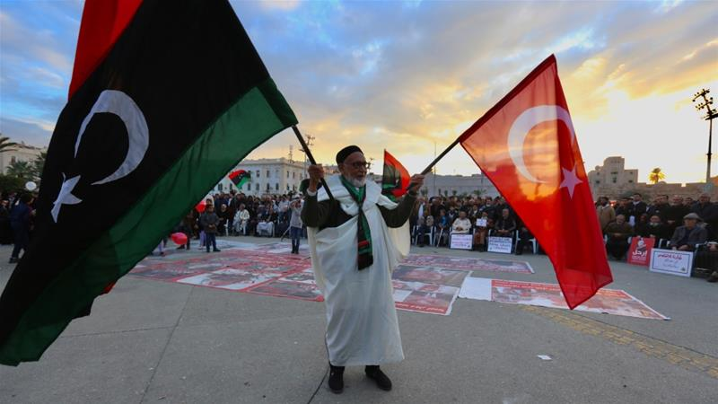 An old man holds flags of Turkey and Libya during a demonstration against renegade military commander Khalifa Haftar and in support of the UN-recognised Government of National Accord in Tripoli [File: Anadolu Agency]