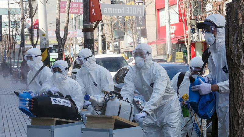 Workers wearing protective gears spray disinfectant as a precaution against the coronavirus at a shopping street in Seoul, South Korea [File: Ahn Young-joon/The Associated Press]