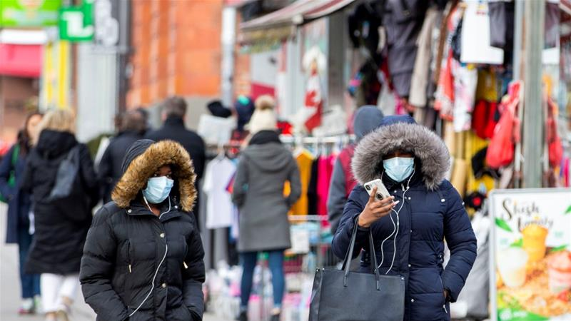 Pedestrians walk in the Chinatown district of downtown Toronto, Ontario on January 28, 2020. Three patients with novel coronavirus have been reported in Canada [Reuters/Carlos Osorio]
