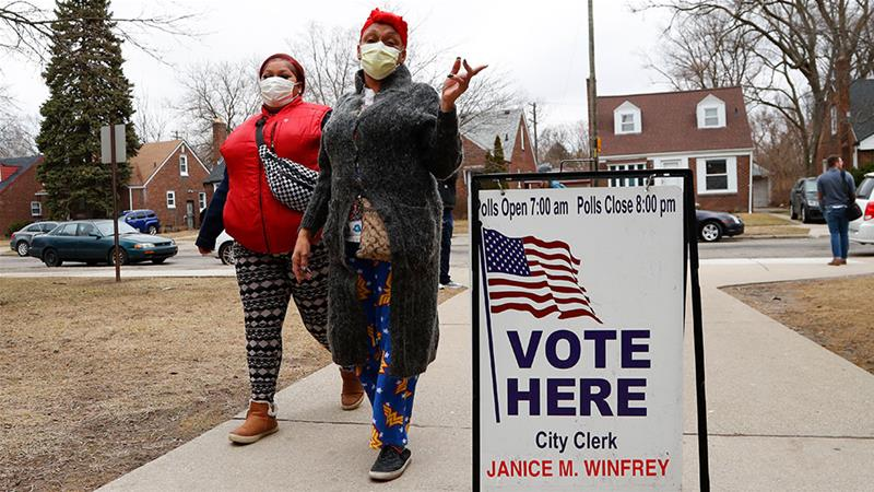 Voters arrive in masks in light of the coronavirus outbreak at Warren E Bow Elementary School in Detroit during Michigan's primary in March [File: Paul Sancya/AP Photo]