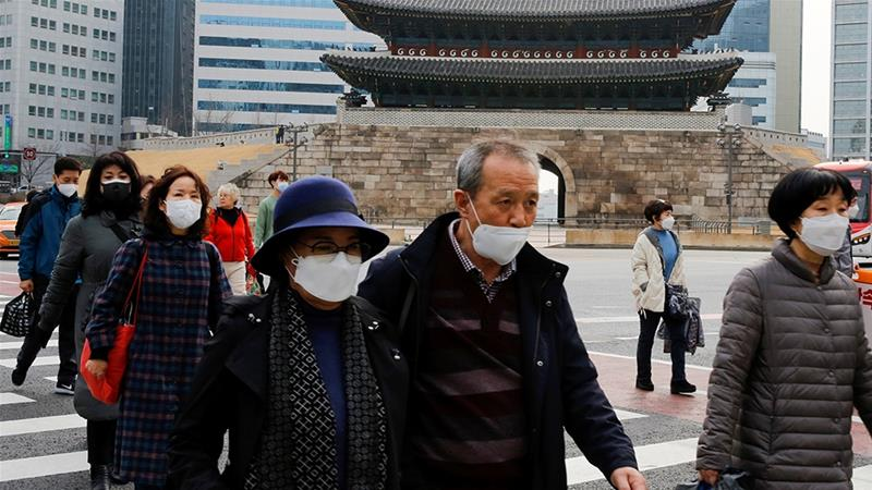 People wearing masks amid the coronavirus outbreak cross a street in downtown Seoul [File: Heo Ran/Reuters]
