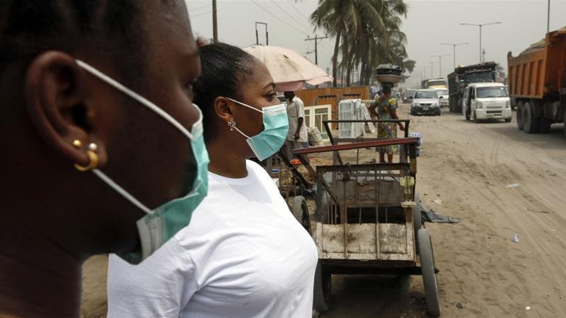 Local residents wear protective face masks on the streets of Lagos, Nigeria [George Osodi/Bloomberg]