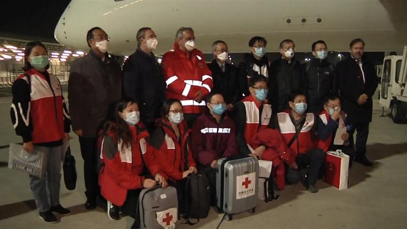 A Chinese team of experts pose for a photograph with head of the Italian Red Cross Francesco Rocca after arriving at Rome's Fiumicino airport with a consignment of medical supplies [Aeroporti di Roma (AdR)/Handout via Al Jazeera]]