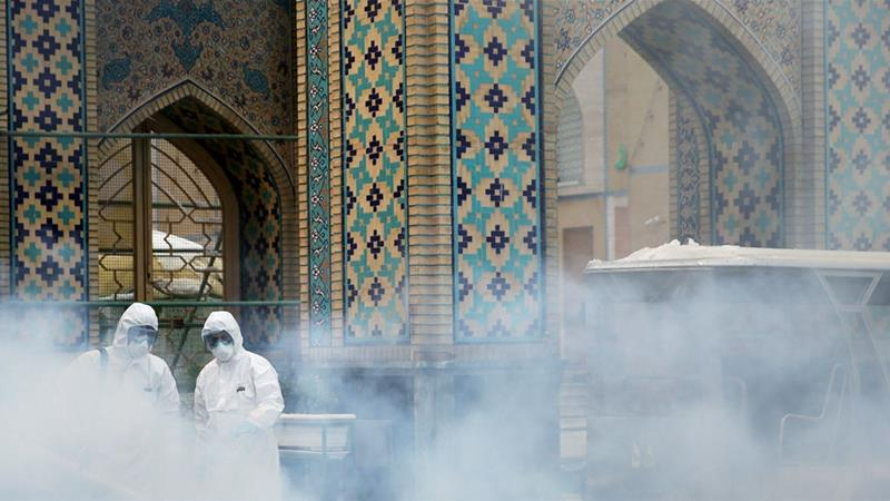 Members of a medical team spray disinfectant to sanitise an outdoor area at Imam Reza's Holy Shrine in Mashhad [WANA via Reuters]