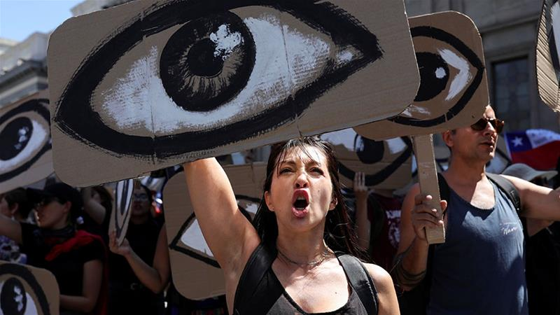 A woman reacts while holding a placard depicting an eye during a protest against Chile''s government, in Santiago, Chile [File; Pablo Sanhueza/Reuters]
