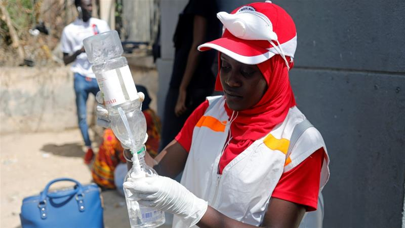 A Red Cross worker in Dakar fills a bottle with sanitising hand gel after Senegal's government ordered all educational establishments to close, one of several new measures to control the spread of coronavirus disease [Zohra Bensemra/Reuters]