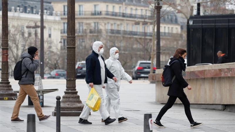 People in protective suits walk on the Champs Elysees Avenue in Paris, France as shops and schools remain closed to curb the outbreak [File: Gonzalo Fuentes/Reuters]