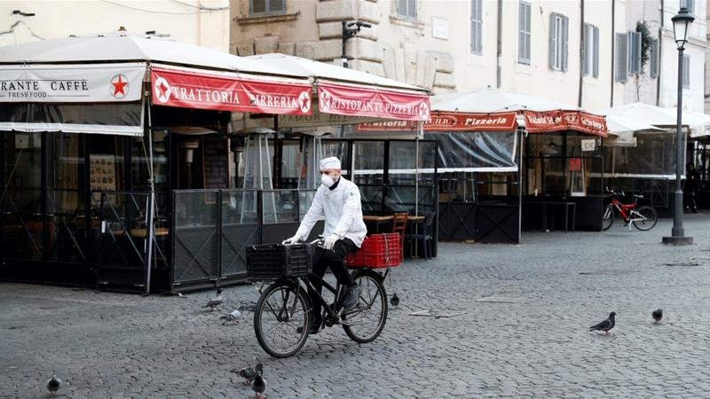 A delivery man wearing a protective mask is seen riding a bicycle at Campo de Fiori, as Italy goes into lockdown to beat the coronavirus, Rome, Italy March 10, 2020. [Remo Casilli/Reuters]