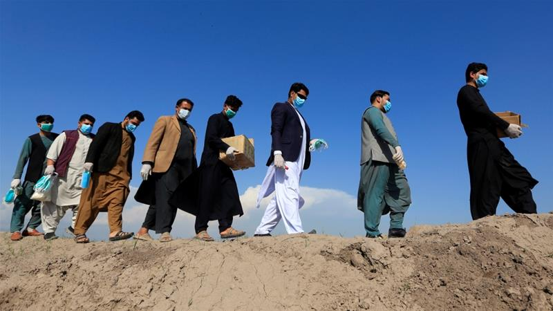 Activists in Afghanistan are distributing face masks to villagers as they spread awareness of the coronavirus infection [Parwiz/Reuters]