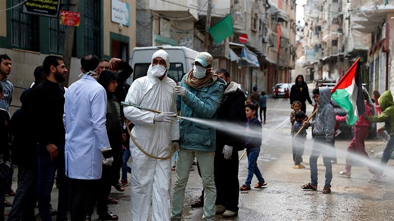 A worker wearing protective gear sprays disinfectant as a precaution against the coronavirus, in Gaza City [Adel Hana/The Associated Press]