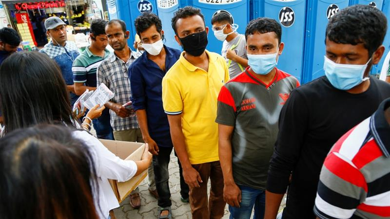 Migrant workers, mostly from Bangladesh, queue to collect free masks and get their temperatures taken in Singapore [File: Feline Lim/Reuters]