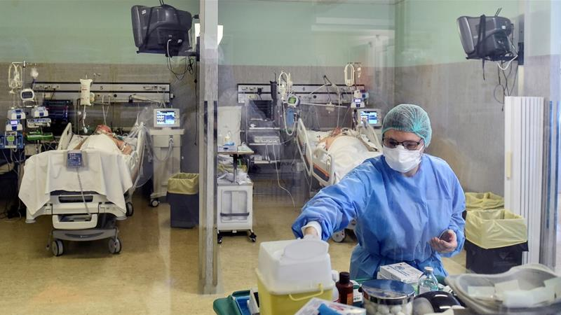 A medical worker wearing a protective mask and suit treats patients suffering from coronavirus disease (COVID-19) in an intensive care unit at the Oglio Po hospital in Cremona, Italy [Flavio Lo Scalzo/Reuters]