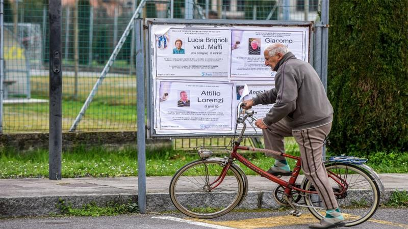 An elderly man riding a bicycle looks at funeral posters displayed outside the small cemetery of Bolgare, Lombardy, on March 23, 2020 during the country's lockdown [Piero Cruciatti/AFP]