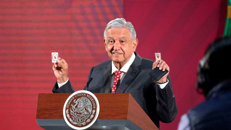 Mexico's President Andres Manuel Lopez Obrador holding up his amulets, which he says serves him as 'protective shields' against the coronavirus disease [File: Handout.Mexico's Presidency/Reuters]