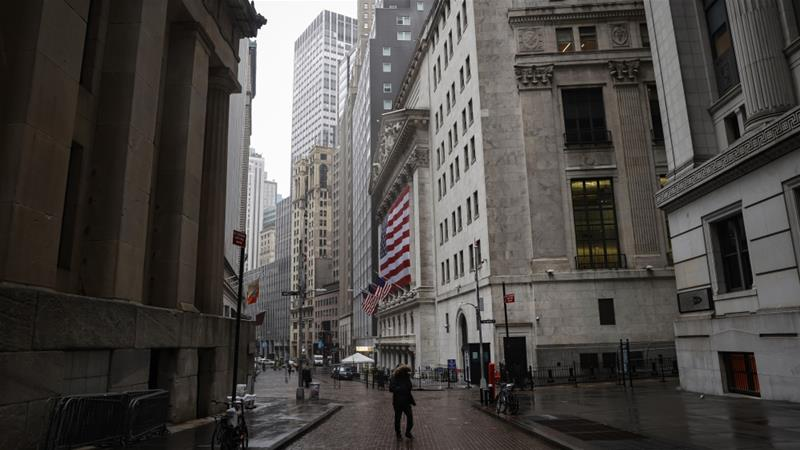 A pedestrian walks on a nearly empty Wall Street, near the New York Stock Exchange in the United States, where the floor is silent, but where trading continues electronically [File: Mike Segar/Reuters]