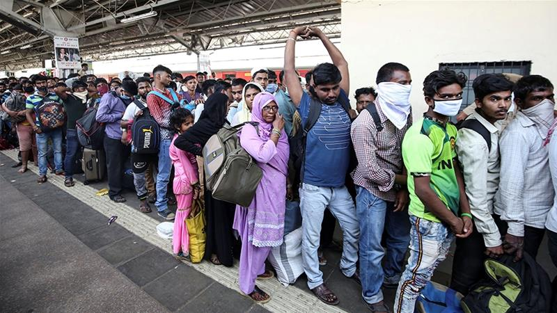 Migrant workers and their families queue to board a train at Mumbai railway station after government imposed restrictions on public gatherings in attempts to prevent spread of COVID-19 [Prashant Waydande/Reuters]