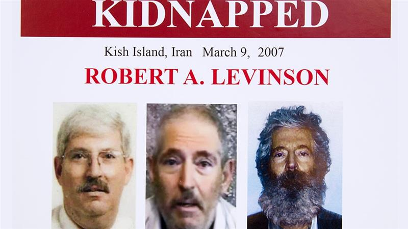 An FBI poster showing a composite image of former FBI agent Robert Levinson, right, of how he would look like after five years in captivity, and an image, a picture before he disappeared, left, [File: Manuel Balce Ceneta/AP Photo]
