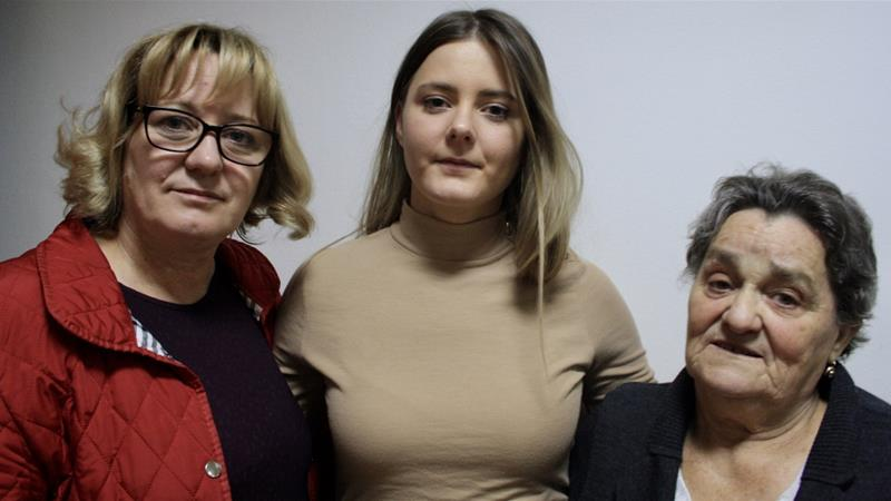 Amela, left, was seven months pregnant with Emina, centre, when her husband was taken by Serbian forces in July 1992. Here they are pictured with Emina's grandmother [Chantal Flores/Al Jazeera]
