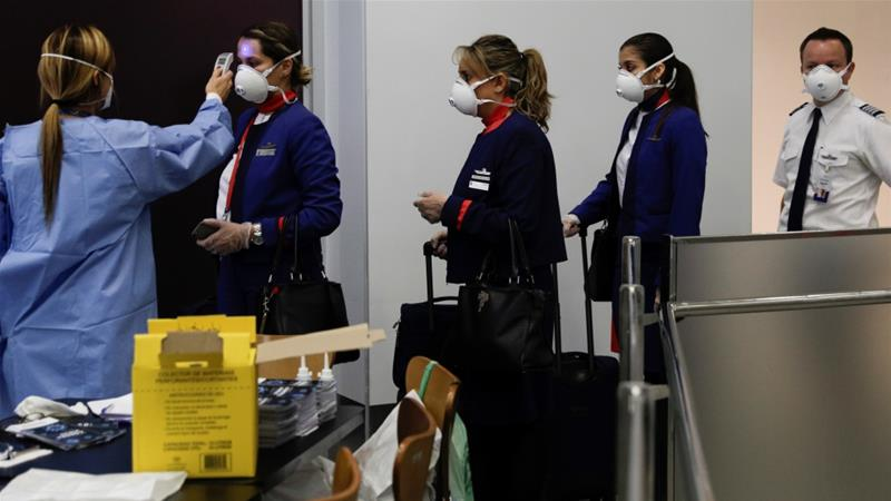 Rio de Janeiro's health surveillance members in protective gear check the body temperatures of flight attendants arriving in Galeao International Airport in Rio de Janeiro, Brazil [File: Ricardo Moraes/Reuters]