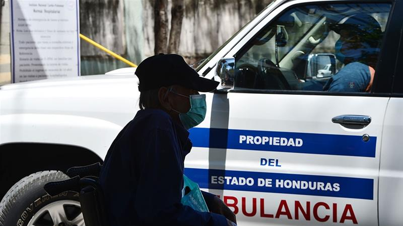 An old man wears a protective face mask to prevent the spread of the new coronavirus as he waits outside the National Cardiopulmonary Hospital in Tegucigalpa [Orlando Sierra/AFP]