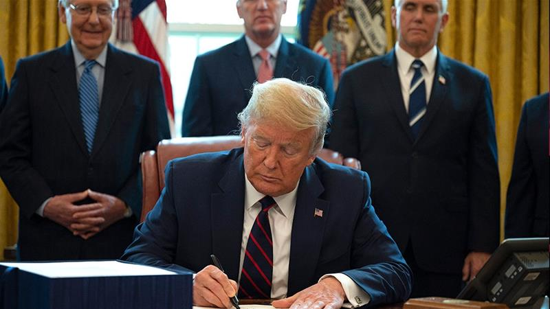 United States President Donald Trump signs the Coronavirus Aid, Relief and Economic Security (CARES) Act, a $2.2 trillion rescue package to provide economic relief amid the coronavirus outbreak [Jim Watson/AFP]