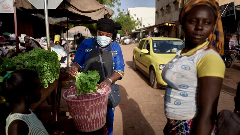 A vegetable vendor wears a mask as as a preventive measure against the spread of COVID-19 in the central market of Bamako [Michele Cattani/AFP]