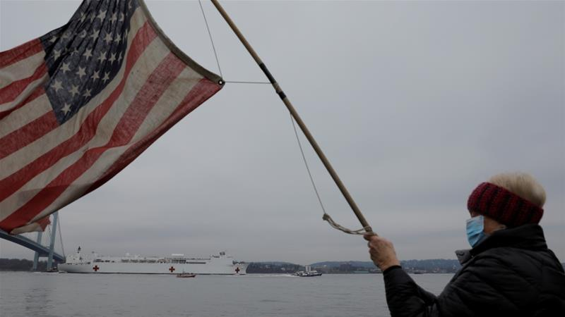 A person waves a United States flag as The USNS Comfort passes under the Verrazzano-Narrows Bridge as it enters New York Harbor, in NY, US, where the government is working with Johnson&Johnson to make a COVID-19 vaccine available in early 2021 [File: Andrew Kelly/Reuters]