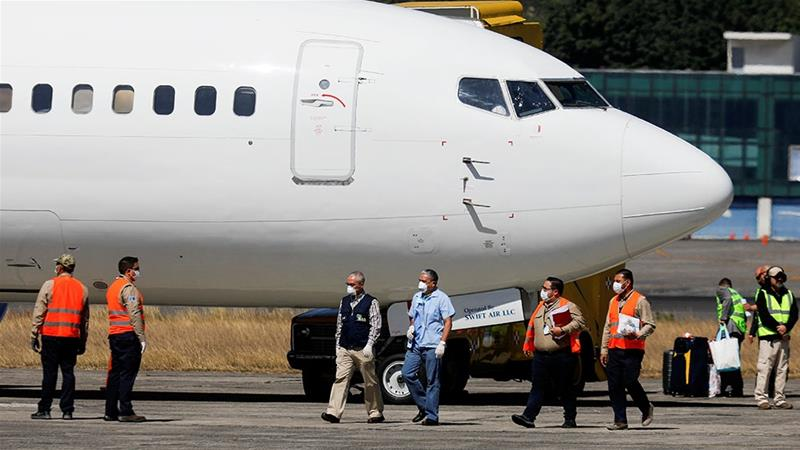 Government officials stand next to a plane carrying migrants deported from the US at La Aurora International airport, in Guatemala City [File: Luis Echeverria/Reuters]