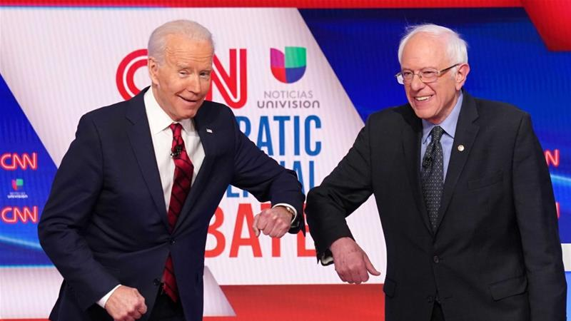 Former Vice President Joe Biden and Senator Bernie Sanders do an elbow bump in place of a handshake as they greet other before the start of the final Democratic debate in Washington, DC [File: Kevin Lamarque/Reuters]