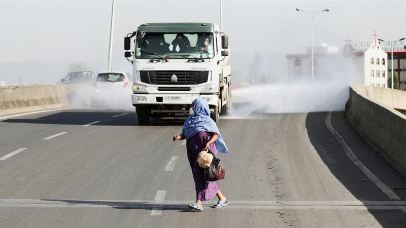 A woman wearing a face mask, runs in front of a truck spraying disinfectant on the street as part of measures to prevent the potential spread of COVID-19 in Addis Ababa, Ethiopia [Tiksa Negeri/Reuters]