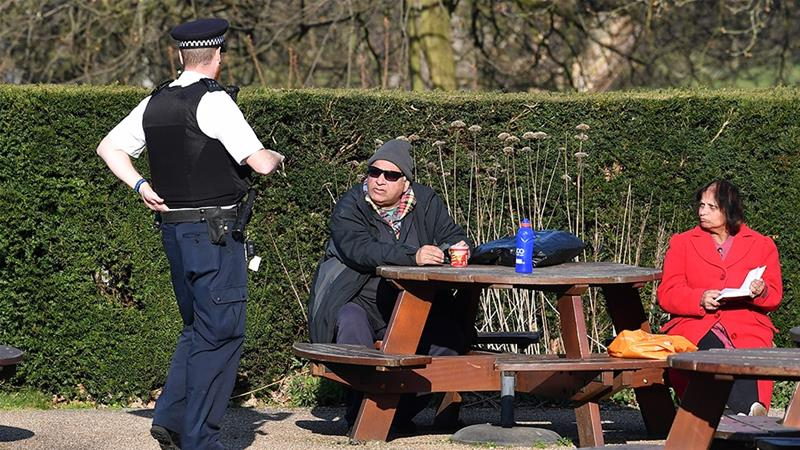 A police officer speaks to a couple sat at a bench in the sunshine in Greenwich Park in London on March 26, 2020 after the government ordered a lockdown to help stop the spread of the new coronavirus [Ben Stansall/AFP]