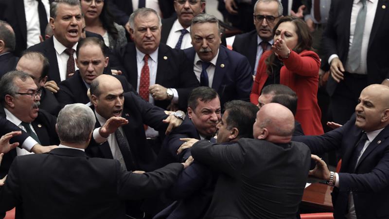 Legislators push each other as a brawl breaks out in Turkey's parliament in Ankara on Wednesday [AP]