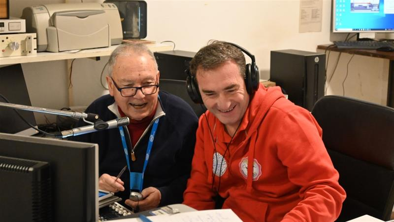 Pino Pagani, left, says elderly listeners who feel even more alone under the quarantine find the radio station comforting [Michele Lori/Al Jazeera]