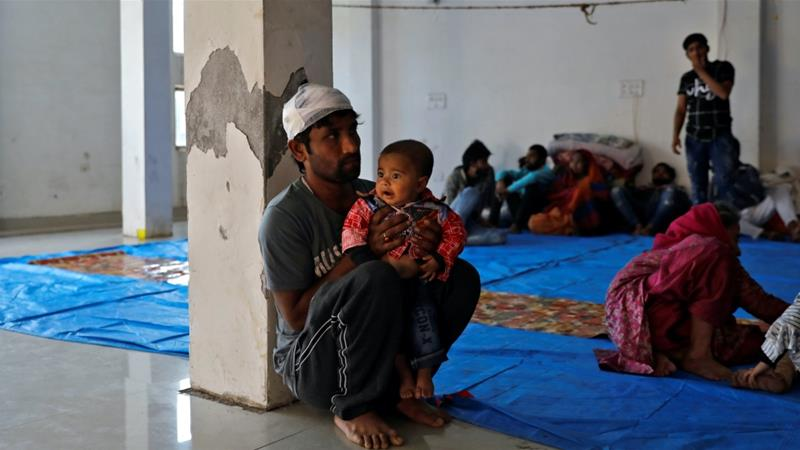 Imran Khan, a Muslim man who was injured during during the violence, sits with his child at Al-Hind hospital, Delhi, India on Feb 27, 2020 [Anushree Fadnavis/Reuters]