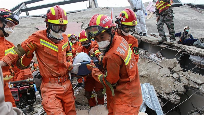 A man is rescued from the rubble of a collapsed hotel in Quanzhou where 71 people were held under observation for coronavirus [AFP]