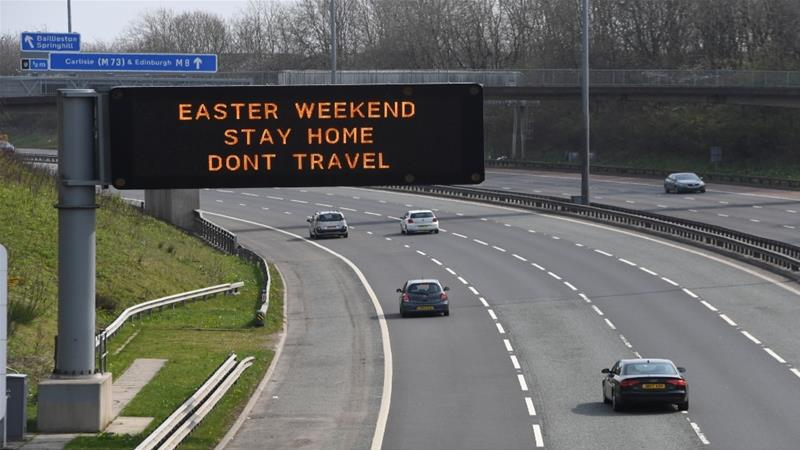 A sign advising people to 'Stay Home' over the Easter weekend is displayed on a stretch of the M8 east of Glasgow on April 10, 2020 [Andy Buchanan/AFP]