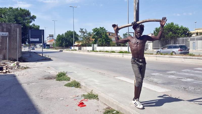 A migrant resident of Castel Volturno ties himself to a lamppost, reenacting the crucifixion of Jesus Christ, as a protest against the conditions endured by migrants in the area [Giovanni Izzo/Al Jazeera]