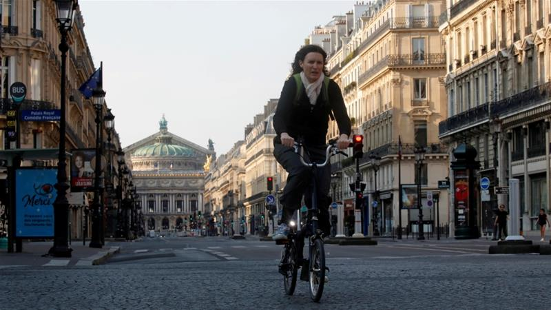 A woman rides her bicycle on almost empty street in Paris, France as the city observes a lockdown to curb the spread of the coronavirus [File: Gonzalo Fuentes/Reuters]