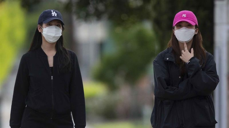 Pedestrians wears face masks in the Chinatown neighbourhood of Los Angeles on April 2, 2020, during the coronavirus outbreak [AP/Damian Dovarganes]