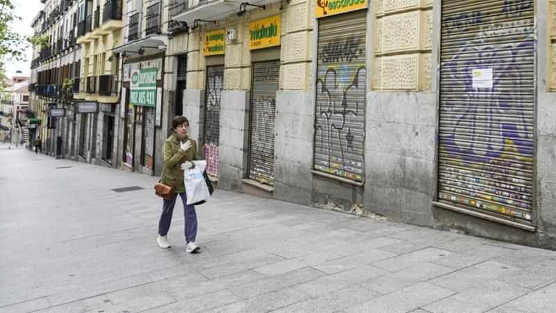 A pedestrian wearing a protective face mask walks by a shuttered outdoor equipment retailer in Madrid, Spain, on Monday, April 13, 2020 [File: Paul Hanna/Bloomberg]