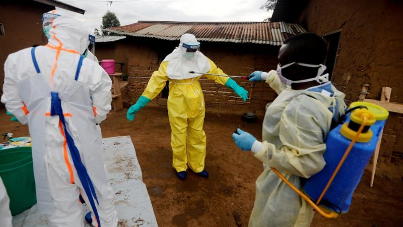 A healthcare worker, who volunteered in the Ebola response, decontaminates his colleague after he entered the house of woman suspected of dying of Ebola in DRC [File: Zohra Bensemra/Reuters]