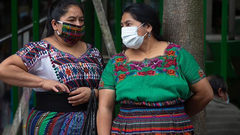 Indigenous women wearing masks to prevent the spread of the new coronavirus stand near the National Palace in Guatemala City [Moises Castillo/Reuters]