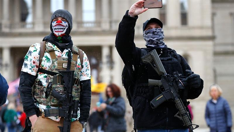 Protesters carry rifles near the steps of the Michigan State Capitol building in Lansing, Michigan, the United States [Paul Sancya/AP Photo]