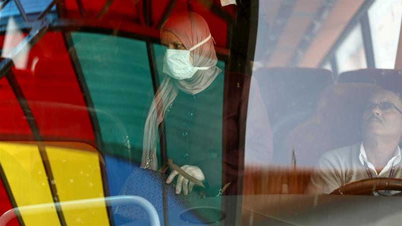 A Palestinian woman, wearing a mask as a preventive measure against coronavirus, alights from a bus upon her return from abroad, at the Israeli-controlled King Hussein/Allenby Bridge crossing in Jericho in the Israeli-occupied West Bank [File: Ammar Awad/Reuters]