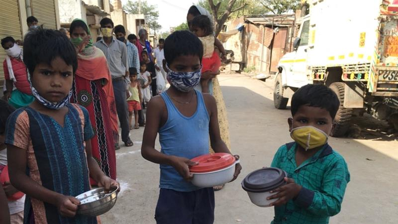 Children queue for rice and legume meals provided by a community organisation in a slum in Kapasheda in Delhi on April 7 [Anumeha Yadav] [Al Jazeera]