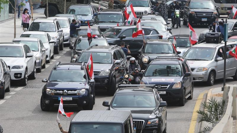 Convoys of cars draped with Lebanese flags blaring loud revolutionary songs tour all of the main centres of the six-month old uprising in Beirut [Aziz Taher/Reuters]