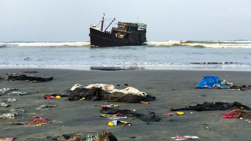 Belongings of Rohingya refugees lay on the shore as their carrier boat remains anchored nearby in Teknaf [File: Suzauddin Rubel/AFP]