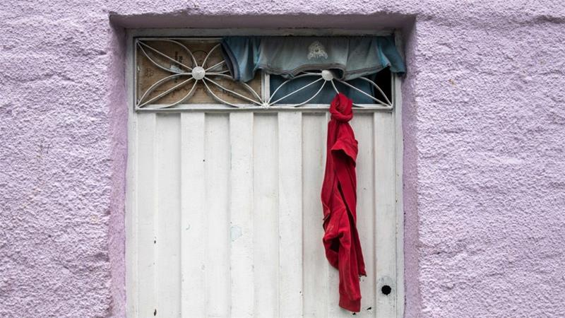A resident of the working-class district of Girardot put a red cloth on his door to indicate those in the home are in need of assistance, in Bogota, Colombia [Nadege Mazars/Al Jazeera]